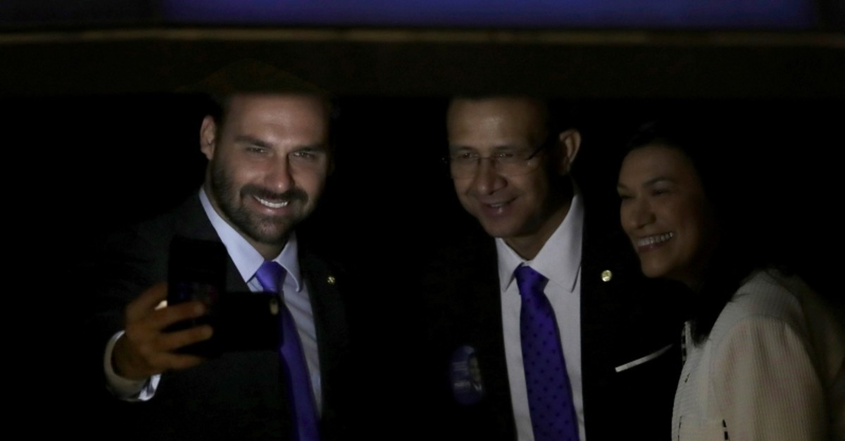 In this Friday, Feb. 1, 2019 file photo, lawmaker Eduardo Bolsonaro, son of Brazil's President Jair Bolsonaro, left, takes a ,selfie, during a swearing-in ceremony, at the National Assembly in Brasilia, Brazil. (AP Photo)