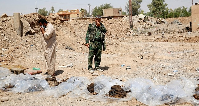 Militia fighters and civilians cover their faces as they stand near bodies recently dug up from a mass grave outside the town of Sulaiman Pek, Iraq Sept. 5, 2014. (Reuters Photo)