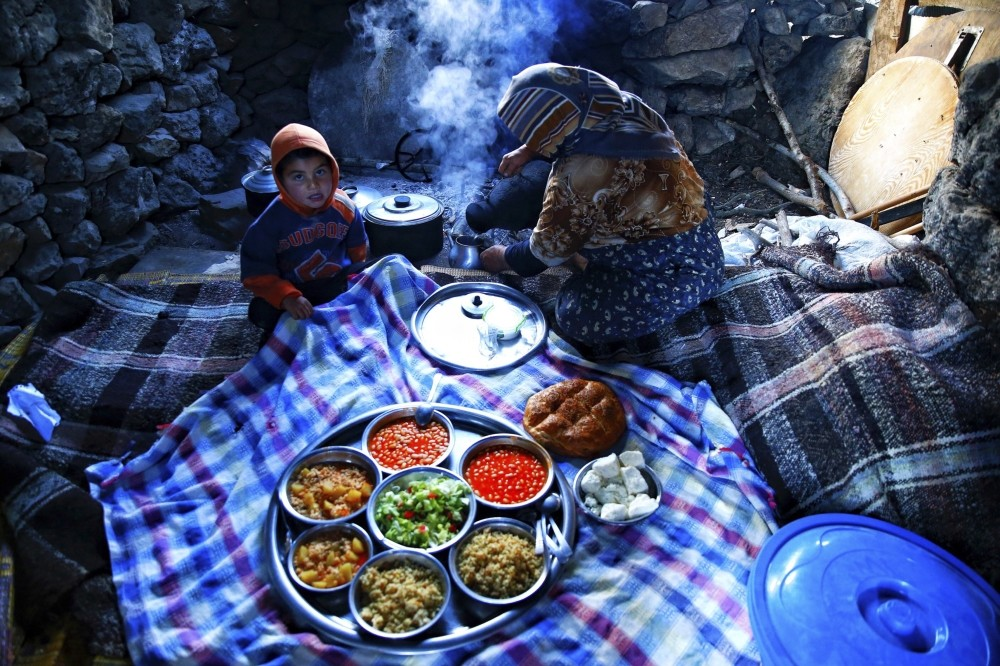 Yu00f6ru00fck iftar tables are adorned with traditional Turkish nomadic foods like bulgur pilaf cooked in smokey pots over a wood-burning fire and keu015fkek