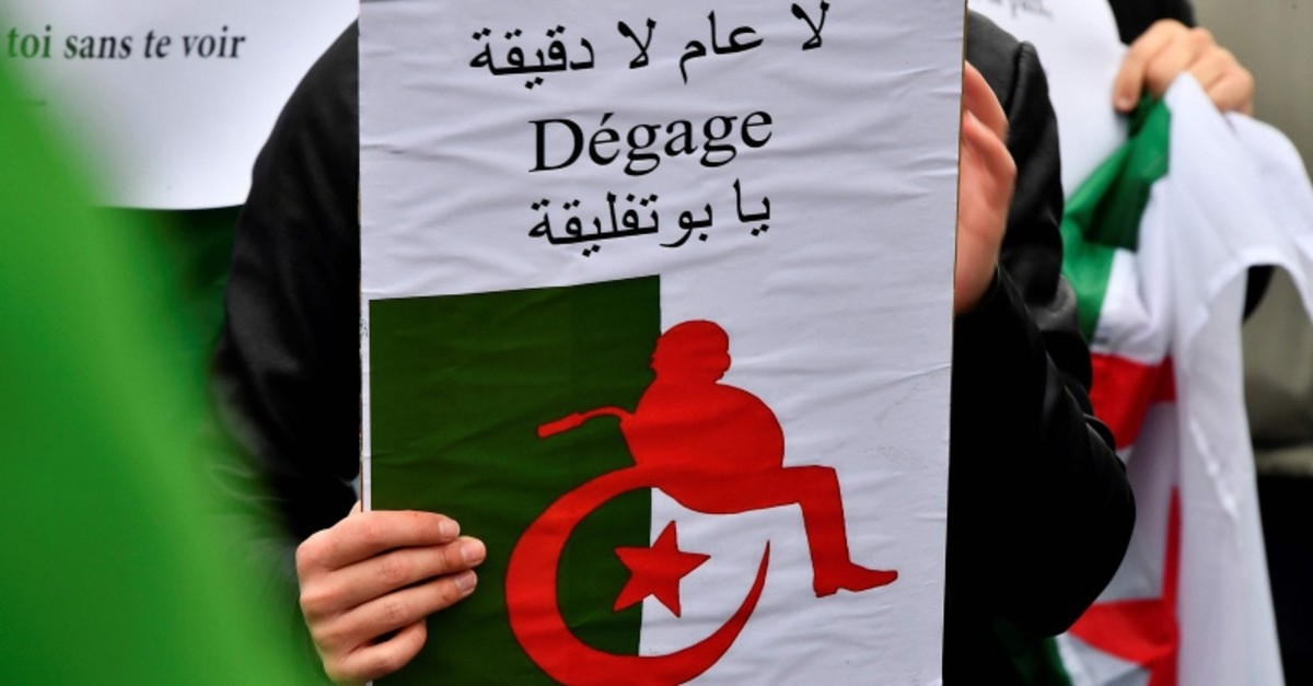 A demonstrator holds a poster representing a silhouette of Algeria's president Abdelaziz Bouteflika on a wheelchair reading ,oust, on the Place de la Victoire in Bordeaux, southwestern France on March 10, 2019. (AFP Photo)