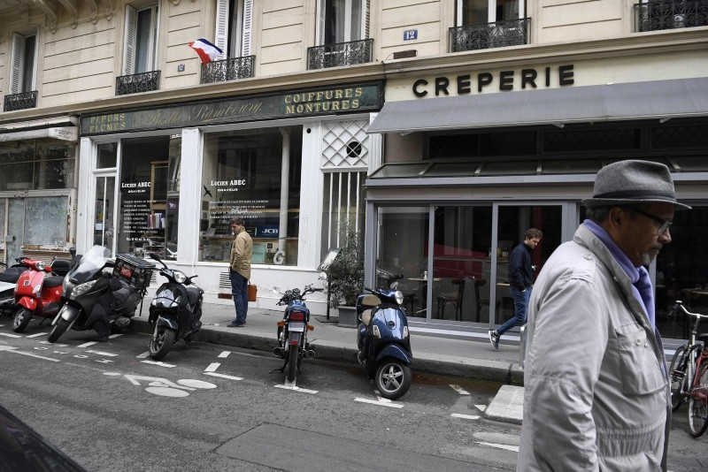 People walk in Monsigny street, on May 13, 2018 in Paris, on the site where a knifeman killed one man and wounded four other people on the eve.  (AFP Photo)