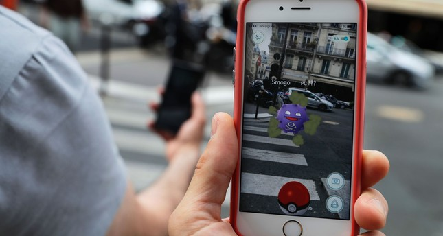 This picture taken on July 26, 2016 near the Louvre museum's pyramide in Paris shows the 'Pokemon Go' app on the screen of a smartphone. AFP Photo