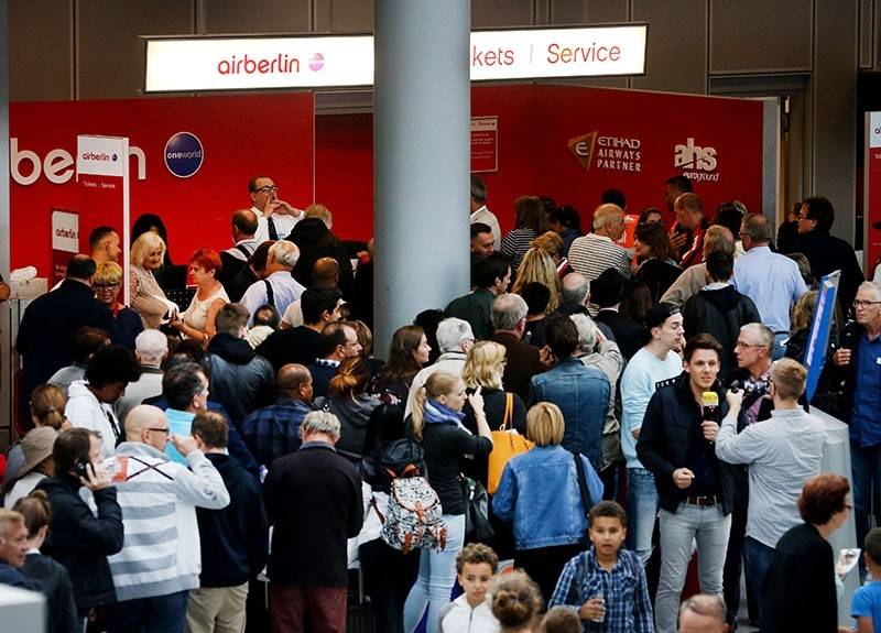 Flight passengers crowd in front of the desk of German airline Air Berlin at the airport in Duesseldorf, western Germany, on September 12, 2017, after the troubled airline had to cancel flights due to ,operational reasons., (AFP Photo)