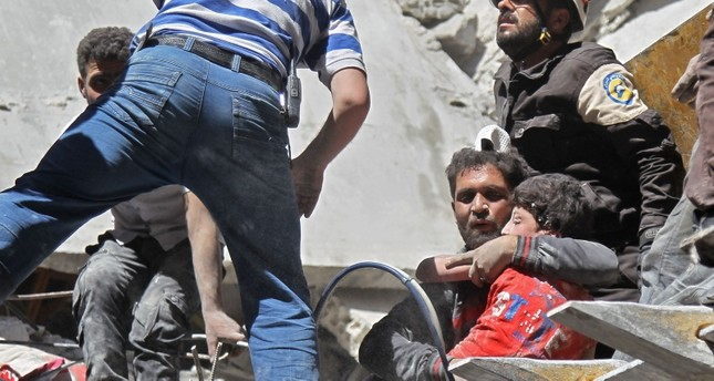 White Helmets rescue a child from the rubble of a building destroyed during an air strike by Assad regime forces on the town of Ariha, in the southern outskirts of Syria's Idlib province on May 27, 2019. (AFP Photo)