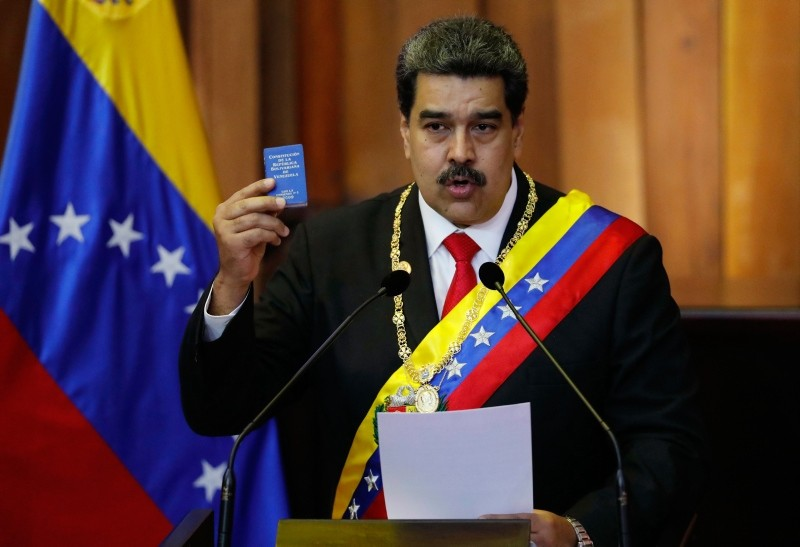 In this Jan. 10, 2019, file photo, Venezuela's President Nicolas Maduro holds up a small copy of the constitution as he speaks during his swearing-in ceremony at the Supreme Court in Caracas (AP Photo)