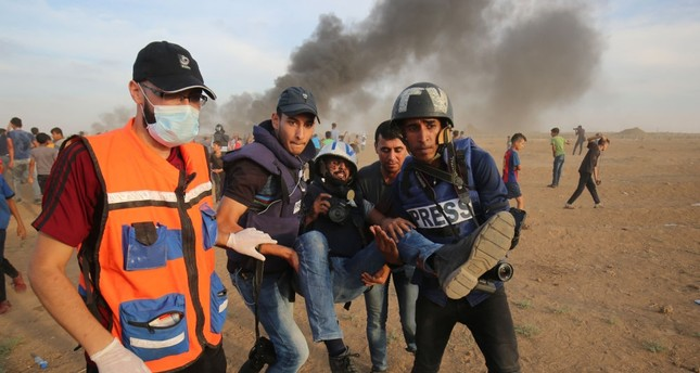 Palestinian paramedics and journalists carry a wounded fellow journalist during clashes with Israeli forces, Gaza Strip, Nov. 5, 2018.