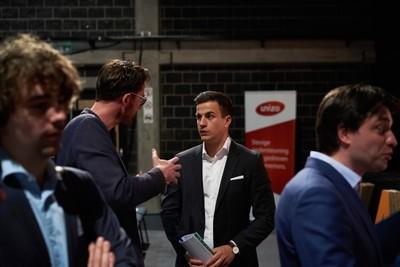 Vlaams Belang party candidate Dries van Langenhove speaks with attendees