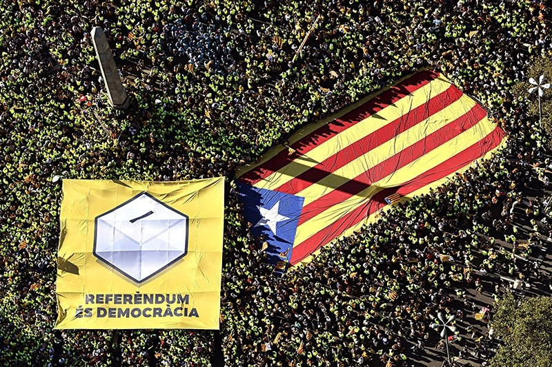 A handout photo made available by ANC shows thousands of people carrying giant Catalan Flag and a banner reading 'Referendum is Democracy' as they gather during the National Day of Catalonia celebrations in Barcelona, Spain, 11 Sept 2017. (EPA Photo)