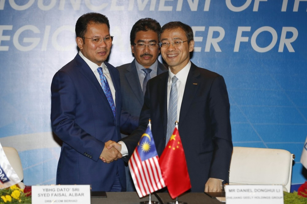 Protonu2019s owner DRB-Hicom Group Director Khalid Abdol Rahman, (L), and Geely Holding Group Chief Financial Officer Daniel Li, (R),shake hands as Malaysian Second Finance Minister Johari Abdul Ghani witnesses during a singing ceremony in Putrajaya.