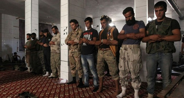 Opposition fighters pray in a safe house in Aleppo during the assault.