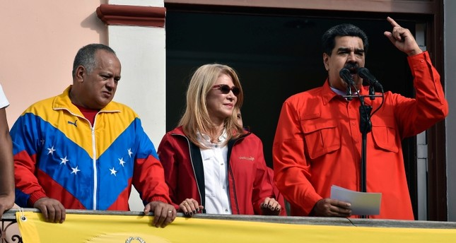 Venezuela's President Nicolas Maduro (R), speaks to a crowd of supporters flanked by his wife Cilia Flores (C) and the head of Venezuela's Constituent Assembly Diosdado Cabello,  during a gathering in Caracas on January 23, 2019. (AFP Photo)