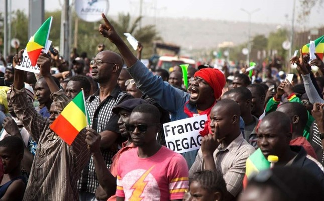 A man shouts as he holds a sign that reads France get out during a protest against French and U.N. forces, Bamako, Jan. 10, 2020. AFP Photo