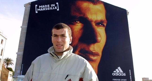 زين الدين زيدان أمام ملصق إعلاني يحمل صورته (الفرنسية)