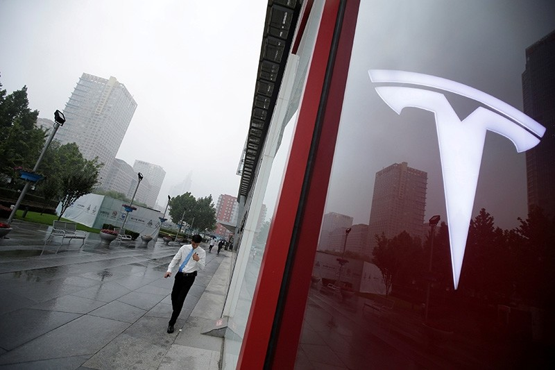 A man walks near a logo of Tesla outside its China headquarters at China Central Mall in Beijing, China July 11, 2018. (Reuters Photo)