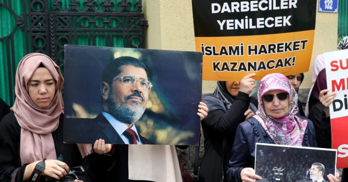 A woman holds a banner reads , The putschists will be defeated, Islamic movement will win , during a symbolic funeral prayer for the Egyptian President Mohamed Morsi on June 18, 2019 in front of the embassy in Ankara. (AFP Photo)