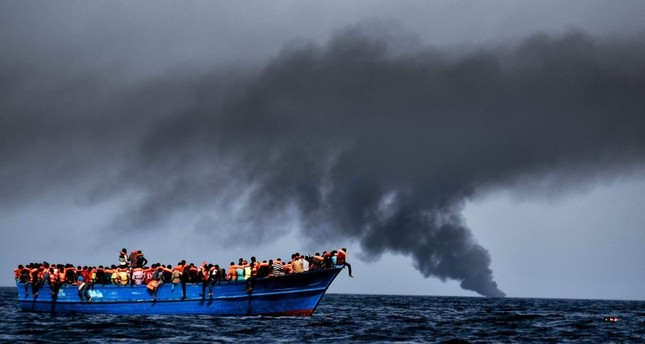 Migrants wait to be rescued by Italian authorities as they drift in the Mediterranean Sea some 20 nautical miles north off the coast of Libya, October 3, 2016.