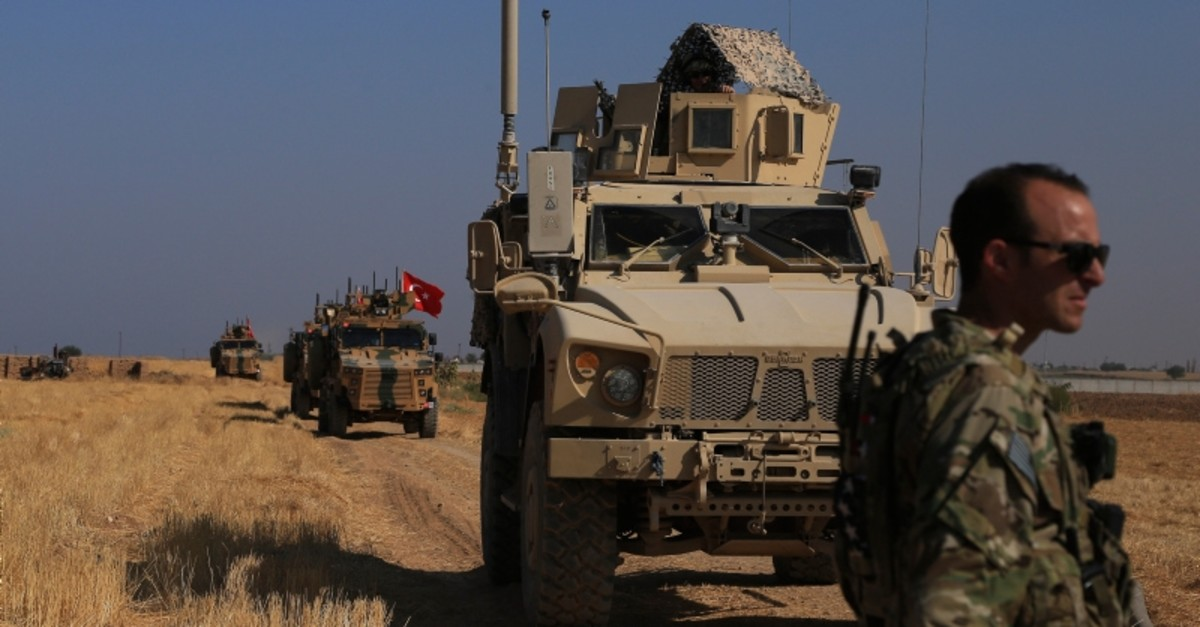 Turkish and American armored vehicles patrol as they conduct joint ground patrol in the ,safe zone, on the Syrian side of the border with Turkey (AP Photo)