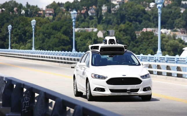 Uber employees test a self-driving Ford Fusion hybrid car in Pittsburgh. (AP Photo)