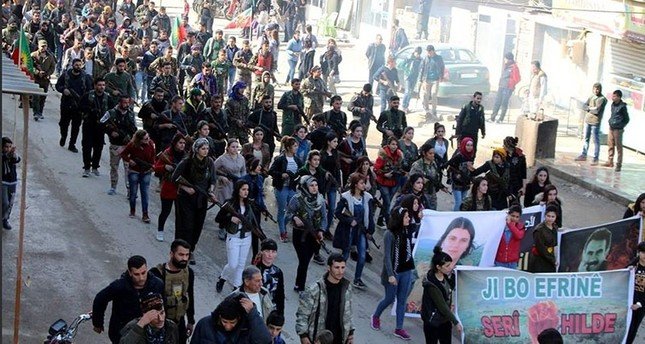 This file photo shows a solidarity march in Syria, in which participants in civilian clothing carry rifles, banners of PKK/PYD/YPG and its jailed leader Abdullah Öcalan. Some 500 terrorists are estimated to cross into Afrin through such convoys.