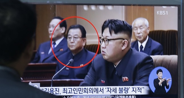 A man watches a TV screen showing a file image of Kim Yong Jin, second from left, a vice premier on education affairs in North Korea's cabinet, and North Korean leader Kim Jong Un. (AP Photo)