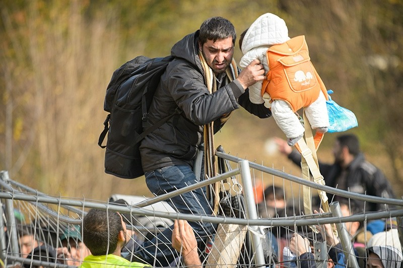 An Austrian serviceman and a migrant help a child to overpass the fence, as migrants and refugees wait to cross the Slovenian-Austrian border, from the Slovenian city of Sentilj, on October 30, 2015 (AFP Photo)