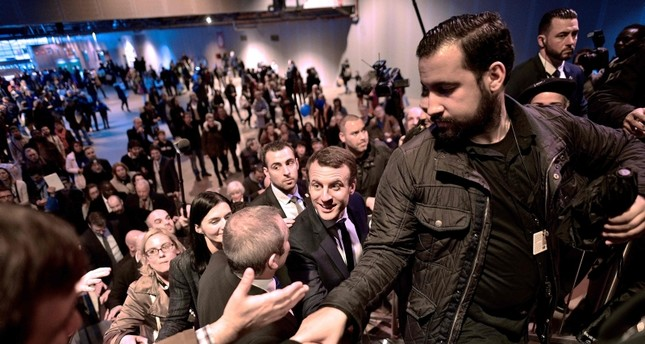 In this file picture taken on March 1, 2017 Emmanuel Macron (C), flanked by head of security Alexandre Benalla (R) shakes hands as he visits Paris' international agriculture fair, in Paris. (AFP Photo)