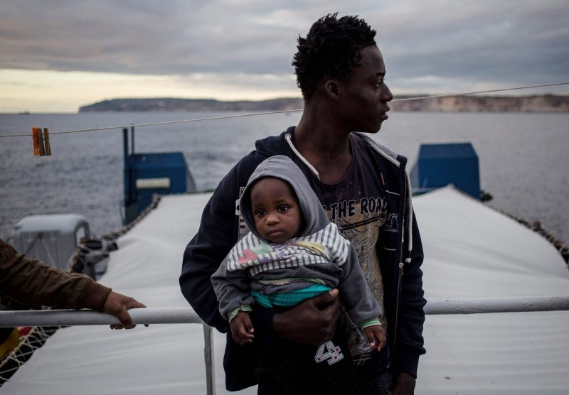 A migrant holds a baby aboard the Dutch-flagged rescue Vessel ,Sea Watch 3, sailing off Malta's coast (Rear) on January 8, 2019 (AFP Photo)