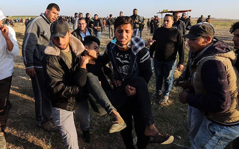 An injured Palestinian man is carried by protesters as they run for cover during a protest along the border with Israel, east of Gaza City in the Gaza strip (AFP Photo)