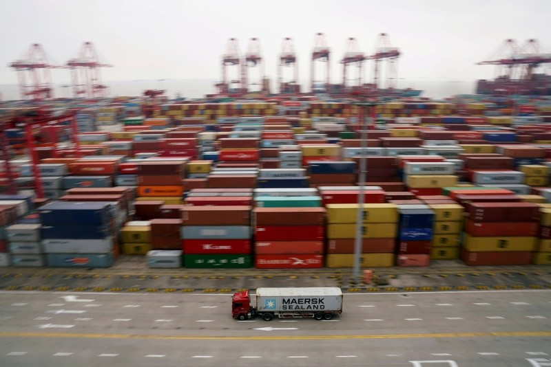 A container truck moves past containers at the Yangshan Deep Water Port in Shanghai, China April 24, 2018. (REUTERS Photo)