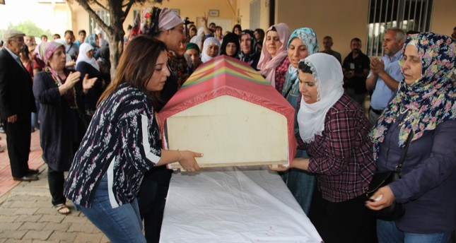 The co-mayor of Kayapınar municipality in Diyarbakır, Fatma Arşimet, is seen on the left carrying the coffin draped in a PKK flag.