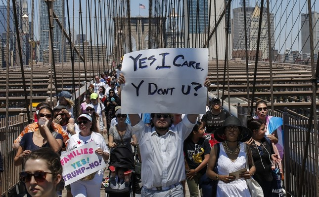 People take part in the nationwide Families Belong Together march as they walk over the Brooklyn Bridge on June 30, 2018 in New York City. AFP Photo
