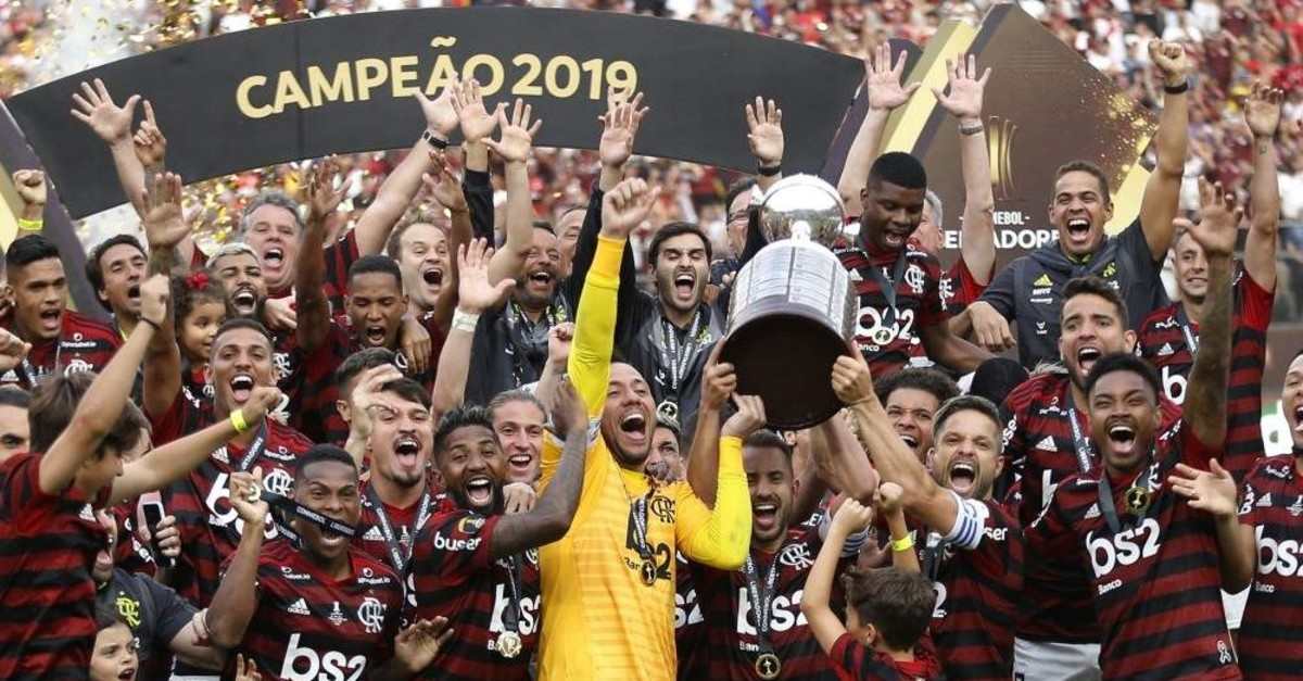 Players from Brazil's Flamengo celebrate on the podium with the trophy after winning the Copa Libertadores final football match by defeating Argentina's River Plate, at the Monumental stadium in Lima, on November 23, 2019. (AFP Photo)