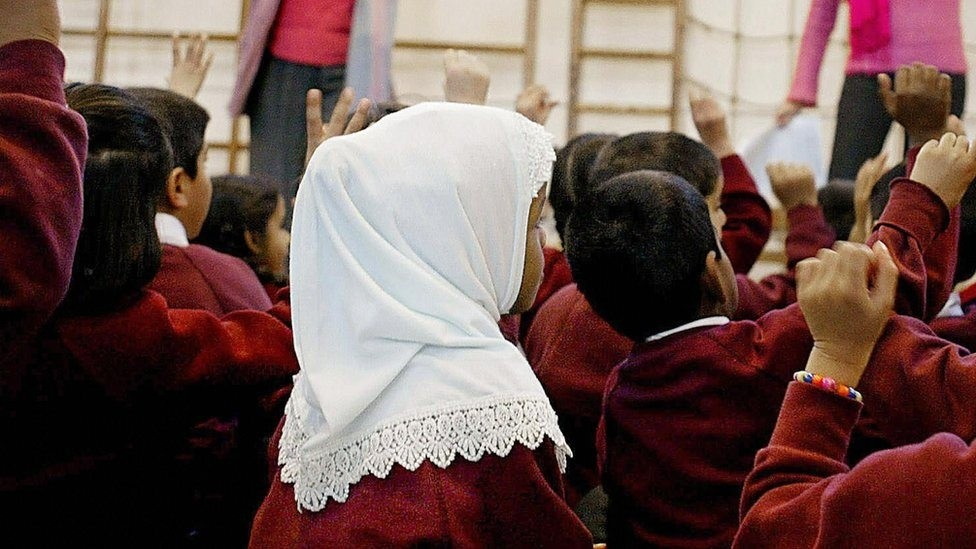 Photo shows a young girl wearing a Muslim headscarf listening as two teachers instruct a class. (AFP Photo)