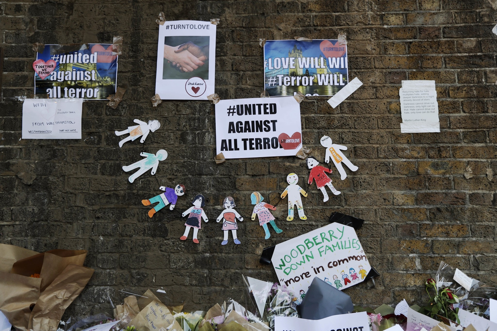 Written tributes of unity are displayed after being placed by the scene of an attack where a man drove into a group of people near a mosque early Monday morning, June 20, 2017. (AP Photo)