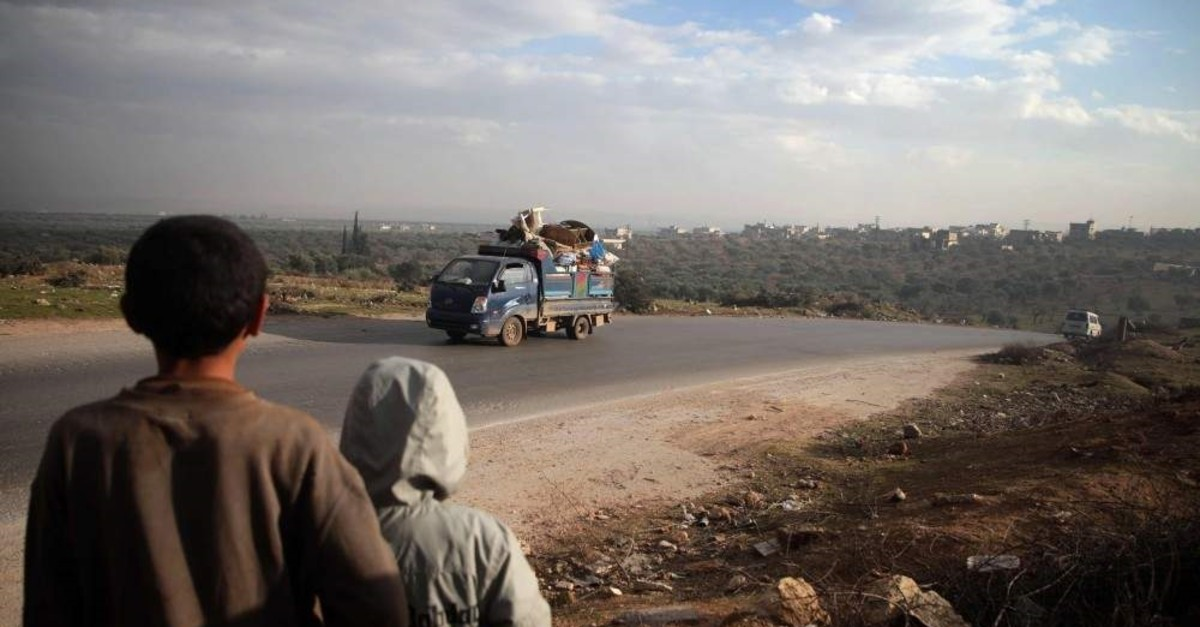 Boys look on at a truck loaded with furniture and belongings in the village of al-Mastumah, near Idlib, Syria, Dec. 24, 2019, amid Assad regime attacks in the area. (AFP Photo)