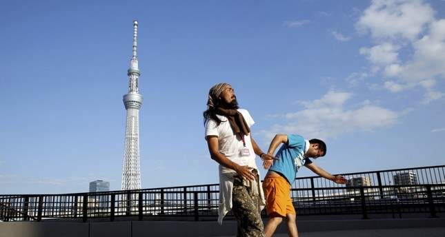 Tokuchika Nishi (L), a 38-year-old homeless man and a member of the dance group, performs with another member in front of Tokyo Sky Tree.