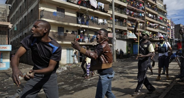 Opposition protesters throw rocks at riot police by hand and with slingshots during clashes with police in Nairobi, Oct. 26.