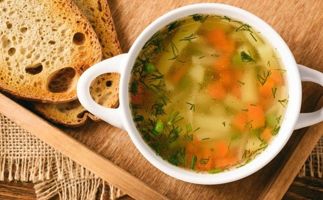 Chicken soup in a white bowl on a wooden tray. iStock Photo