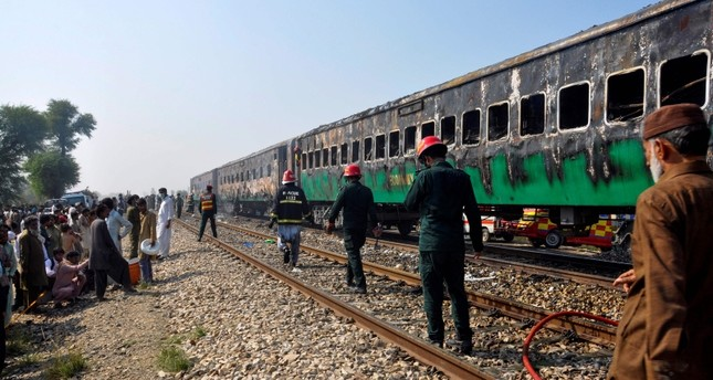 Rescue workers walk past  a train damaged by a fire in Liaquatpur, Pakistan, Thursday, Oct. 31, 2019. (AFP Photo)