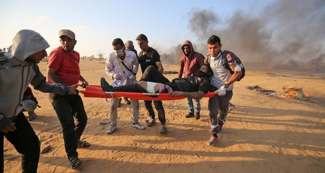 Palestinian medics carry on a stretcher a protester injured during clashes with Israeli forces along the border east of Khan Yunis in the southern Gaza Strip on May 15, 2018. (AFP Photo)