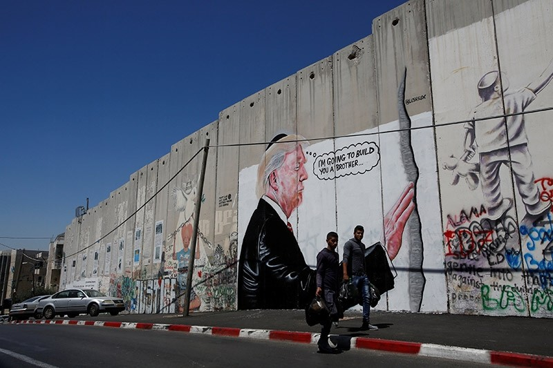 Palestinians walk past a graffiti depicting U.S President Donald Trump on the controversial Israeli barrier in the West Bank town of Bethlehem August 4, 2017. (Reuters Photo)