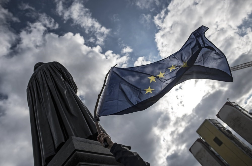 A man waves an EU flag in front of the Martin Luthger Statue during a pro-European Union rally called 'Pulse of Europe' at Neumarkt square in Dresden, Germany March 12.