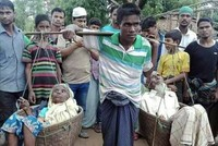 Young Rohingya man carries elderly parents in baskets to escape Myanmar violence