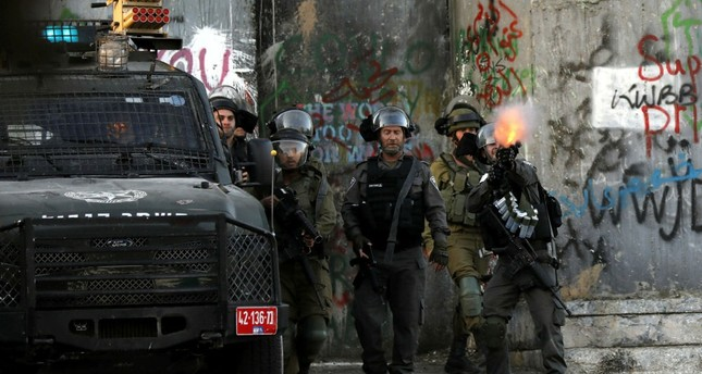 Israeli soldiers shoot tear gas at Palestinian protesters during clashes following a protest in the West Bank city of Bethlehem, July 19.
