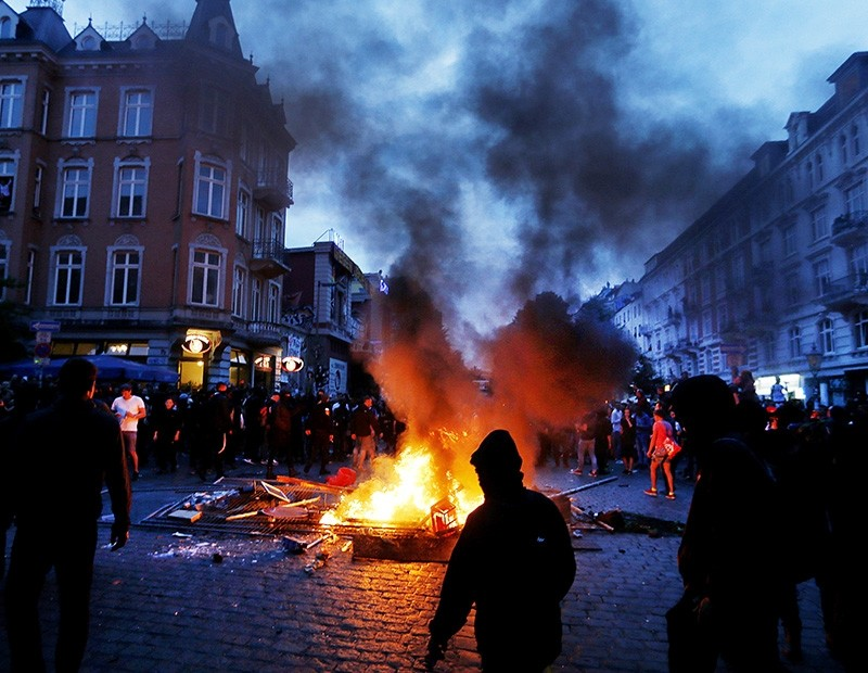 Protesters stay between fires on a street during a protest against the G-20 summit in Hamburg, northern Germany, Friday, July 7, 2017. (AP Photo)