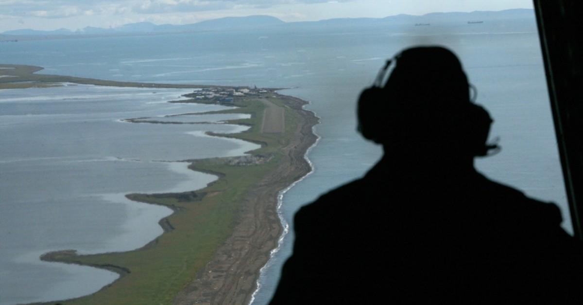 In this Aug. 7, 2008, file photo, Aviation Maintenance Tech 2, John Ferrari looks out of the back of a U.S. Coast Guard C-130 as he surveys the coast near the village of Kivalina, Alaska, during a surveillance flight to the Arctic (AP Photo)