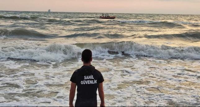عنصر من خفر السواحل التركي يراقب قارباً لمهاجرين غير نظاميين (الأناضول)