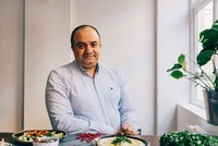 Chef Imad Alarnab furiously chops onions and stirs giant pots of bubbling stew as he prepares dinner.
