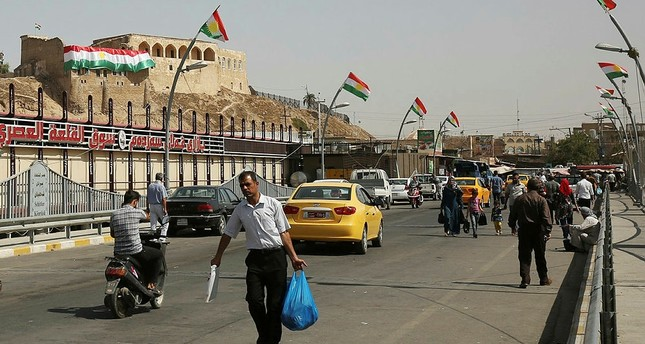 Iraqis walk past Kurdish flags in central Kirkuk on September 24, 2017, on the eve of the independence referendum for the Kurdistan region. (AFP Photo)