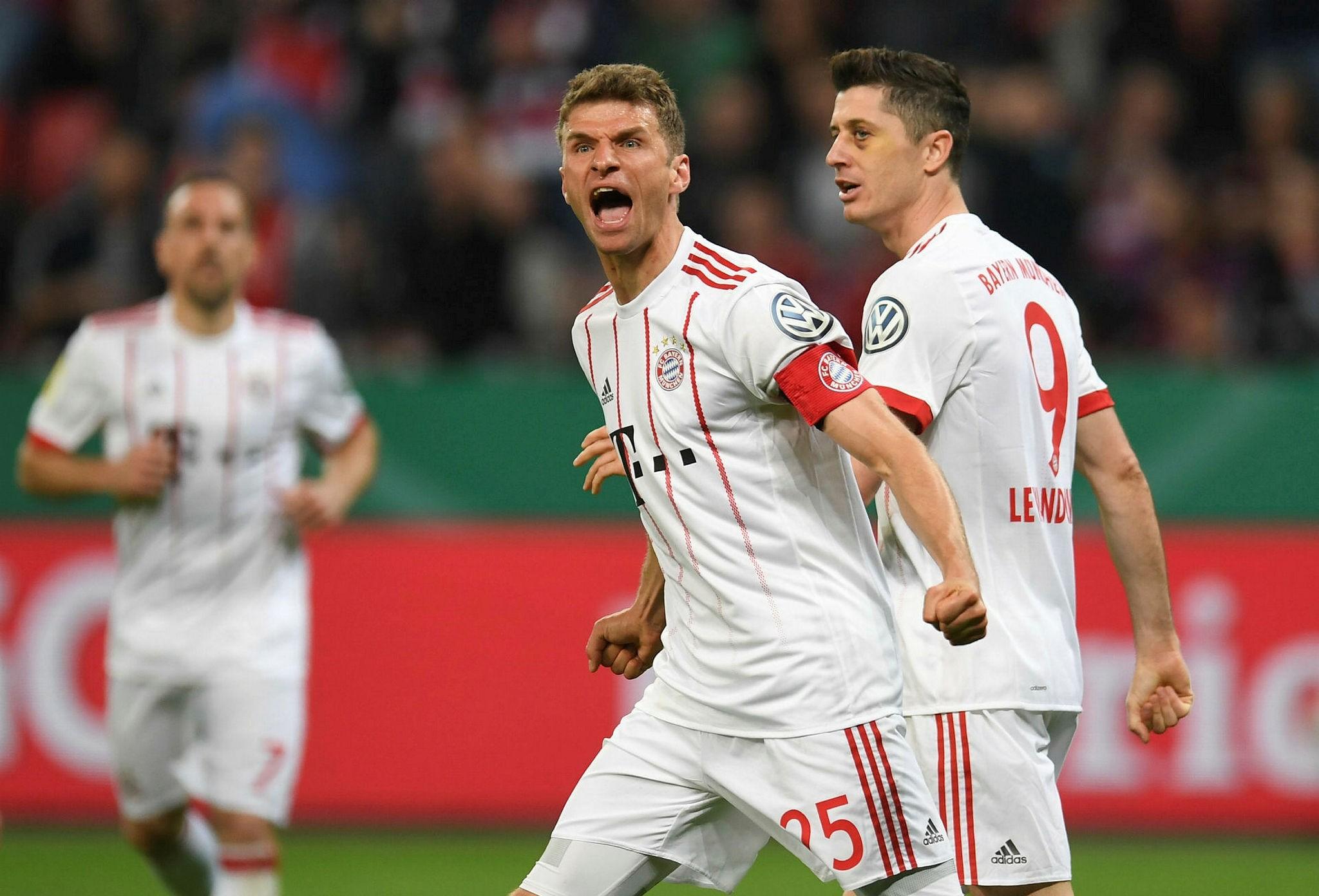 Bayern Munich's German forward Thomas Mueller (L) celebrates next to Polish forward Robert Lewandowski after scoring during the German football Cup DFB Pokal semifinal match Bayer 04 Leverkusen vs Bayern Munich in Leverkusen, Germany, April 17, 2018.